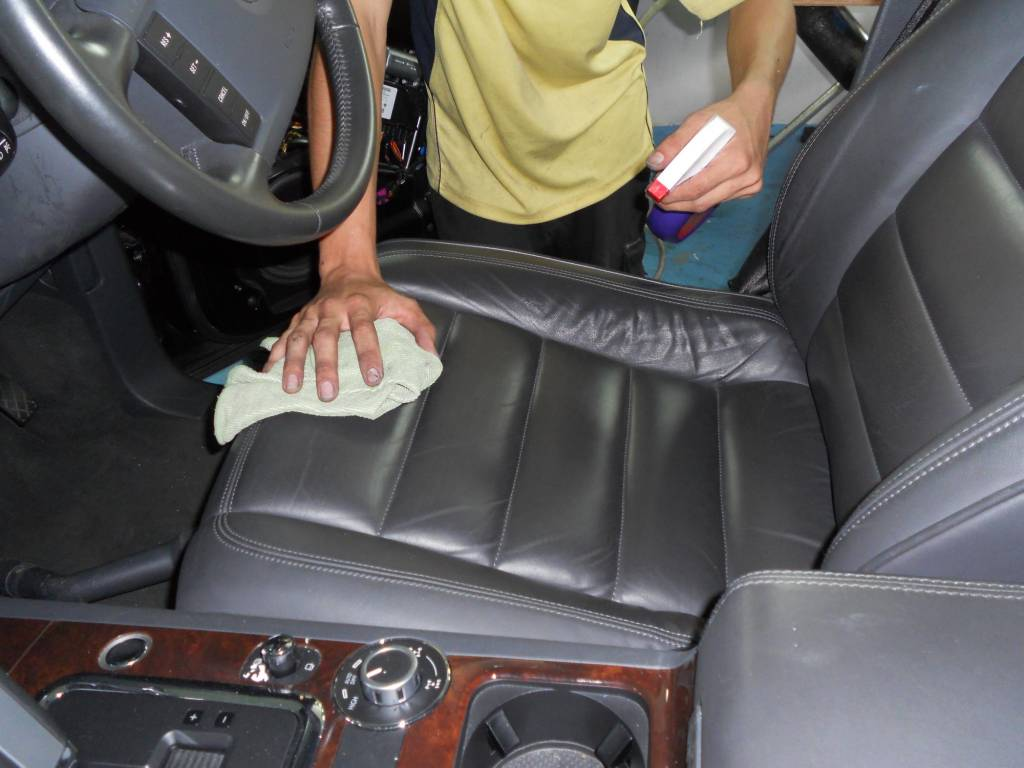 Cleaning leather car seats with a cloth and spray