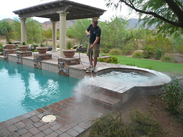 man power washing pool's deck
