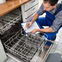 plumber finishing installing a dishwasher