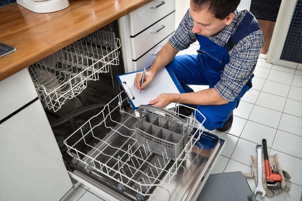 plumber finishing installing a dishwasher