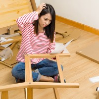 young woman trying to figure out how to assemble a chair