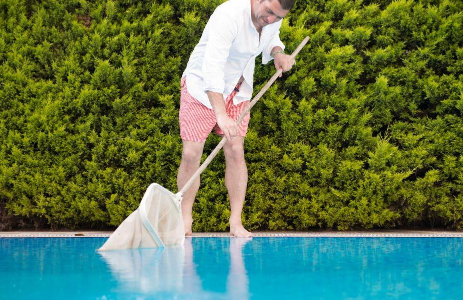 man skimming pool