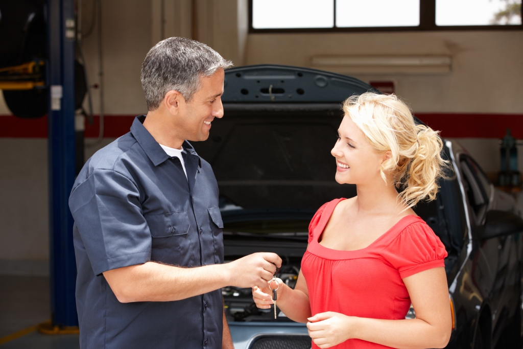 mechanic giving car key to a woman client