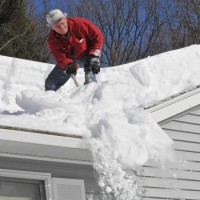 man on top of the roof removing snow