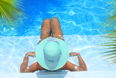 woman in a hat sitting in pool and relaxing