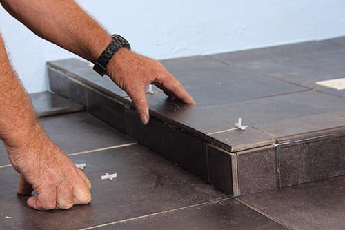 man tiling the floor dark tile