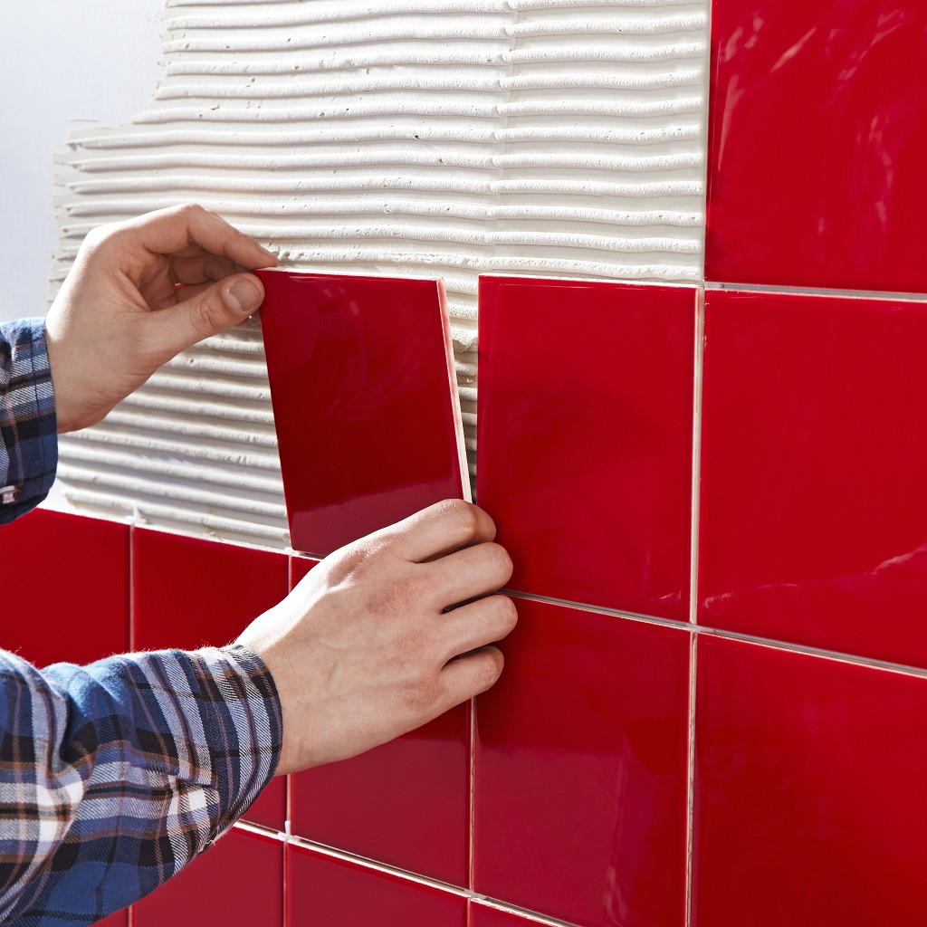 man installing red tile