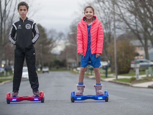 young boy and girl riding a hoverboard outside