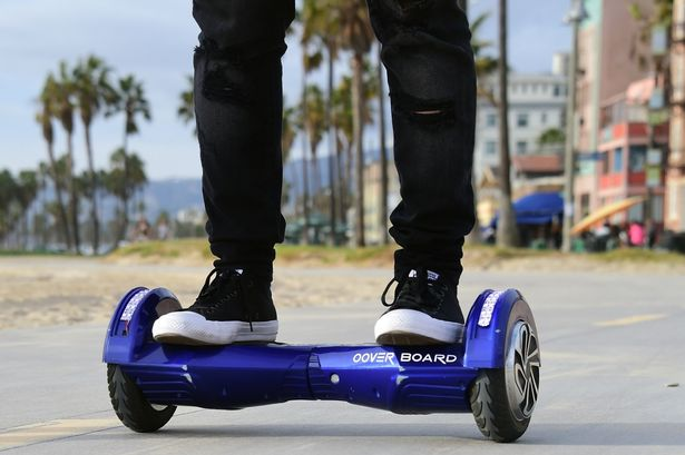 person in black jeans riding a blue hoverboard