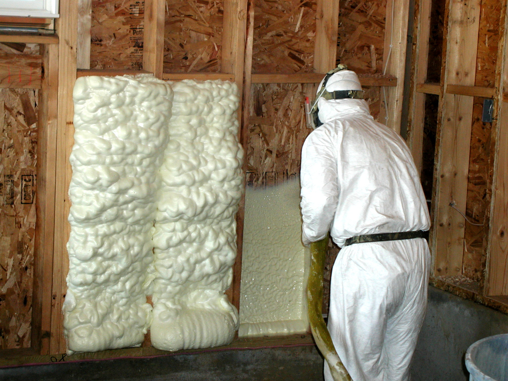 man in white protective constume insulating wall