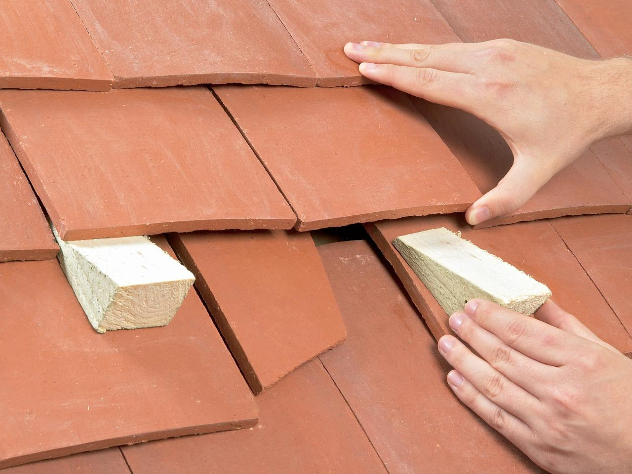 man sticking wooden blocks under roof tiles