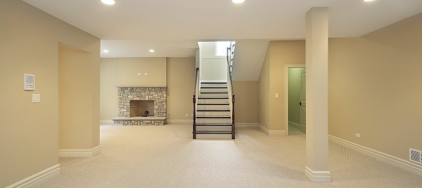 remodeled empty basement with fireplace