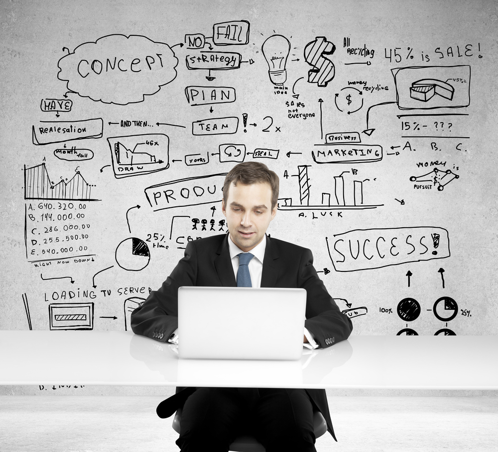 ... Businessman In A Suit In Front Of Laptop Developing A Business Plan