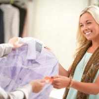 woman picking up clothes from the drycleaners
