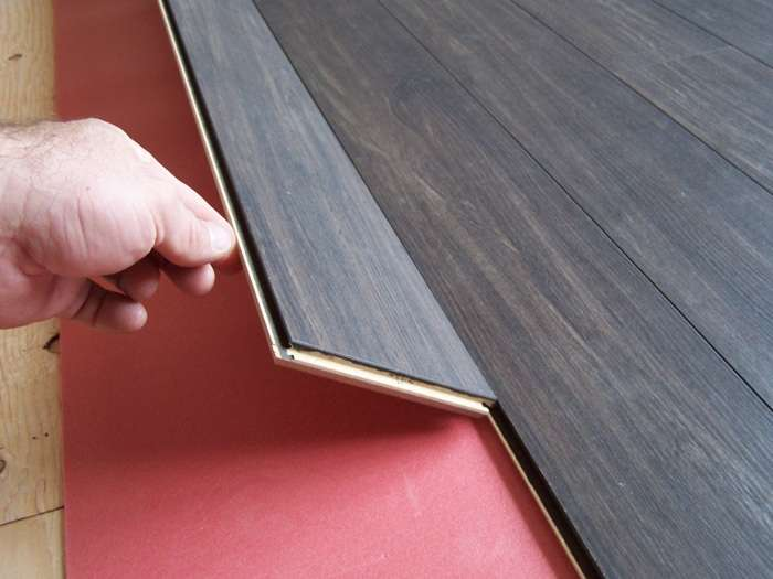 11 steps how to install laminate flooring hirerush blog laminate floor installation man installing dark laminate solutioingenieria Image collections