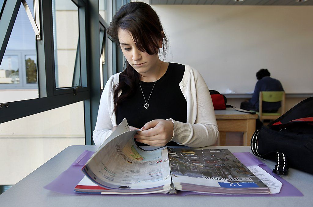 young woman at the desk reading foreign language textbook
