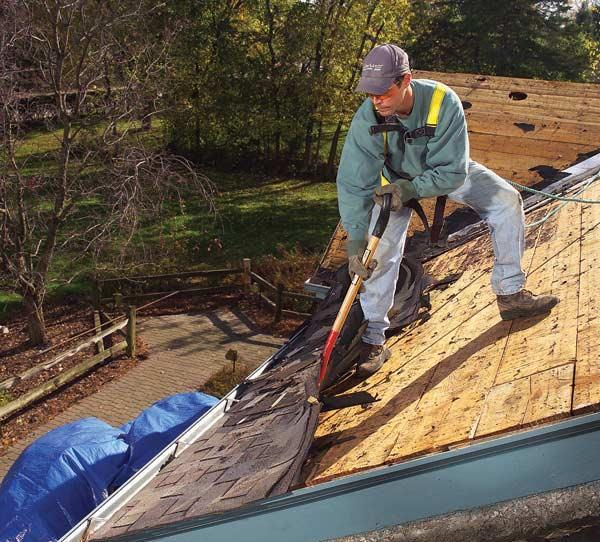 man tearing off old roof shingles