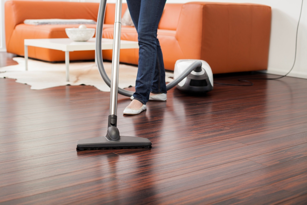 ... Woman Vacuuming Dark Hardwood Floor
