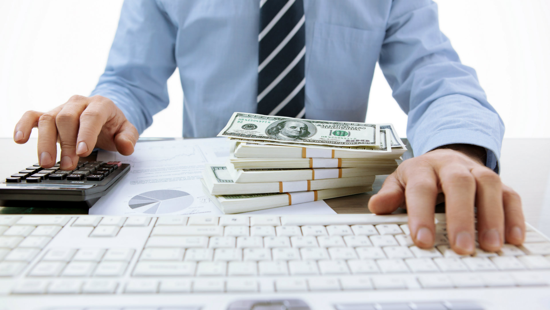 accountant in front of computer with money