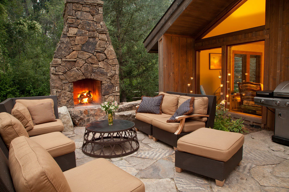 Outdoor Fireplace Near The House With Soft Furniture On Patio