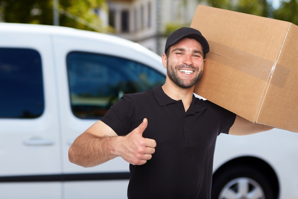 smiling mover holding a cardboard box