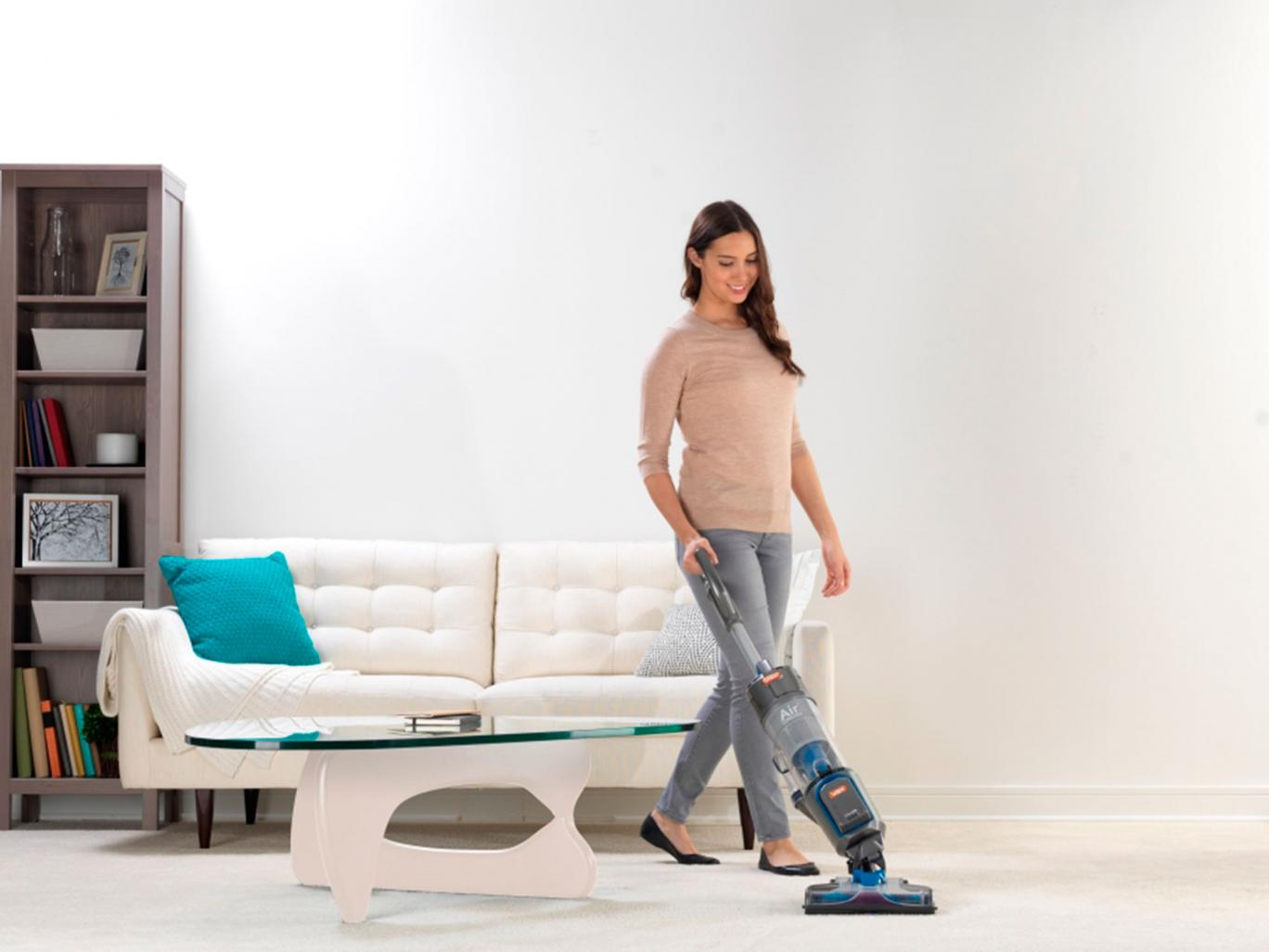 woman vacuuming the carpet with an upright vacuum