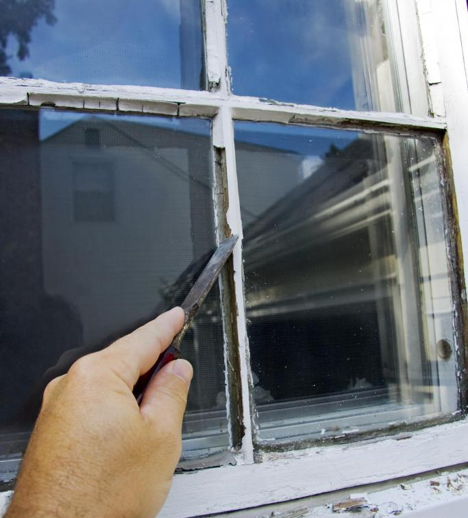 man scraping the window before window pane replacement