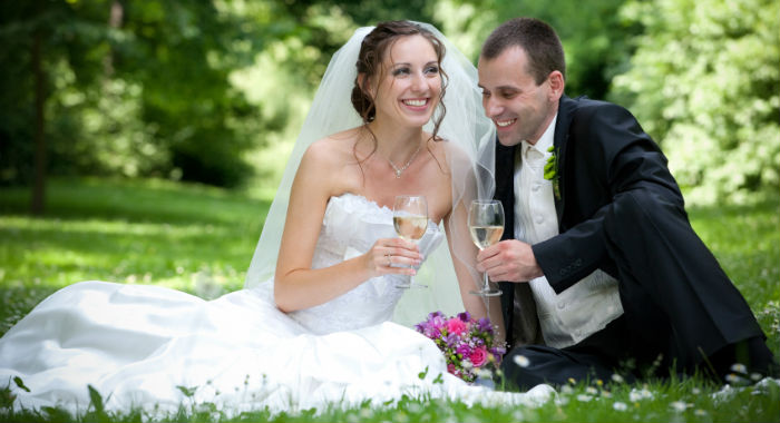wedding on a budget a bride and a groom sitting on the grass