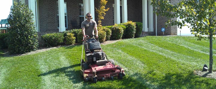 lawn care contractor mowing the grass