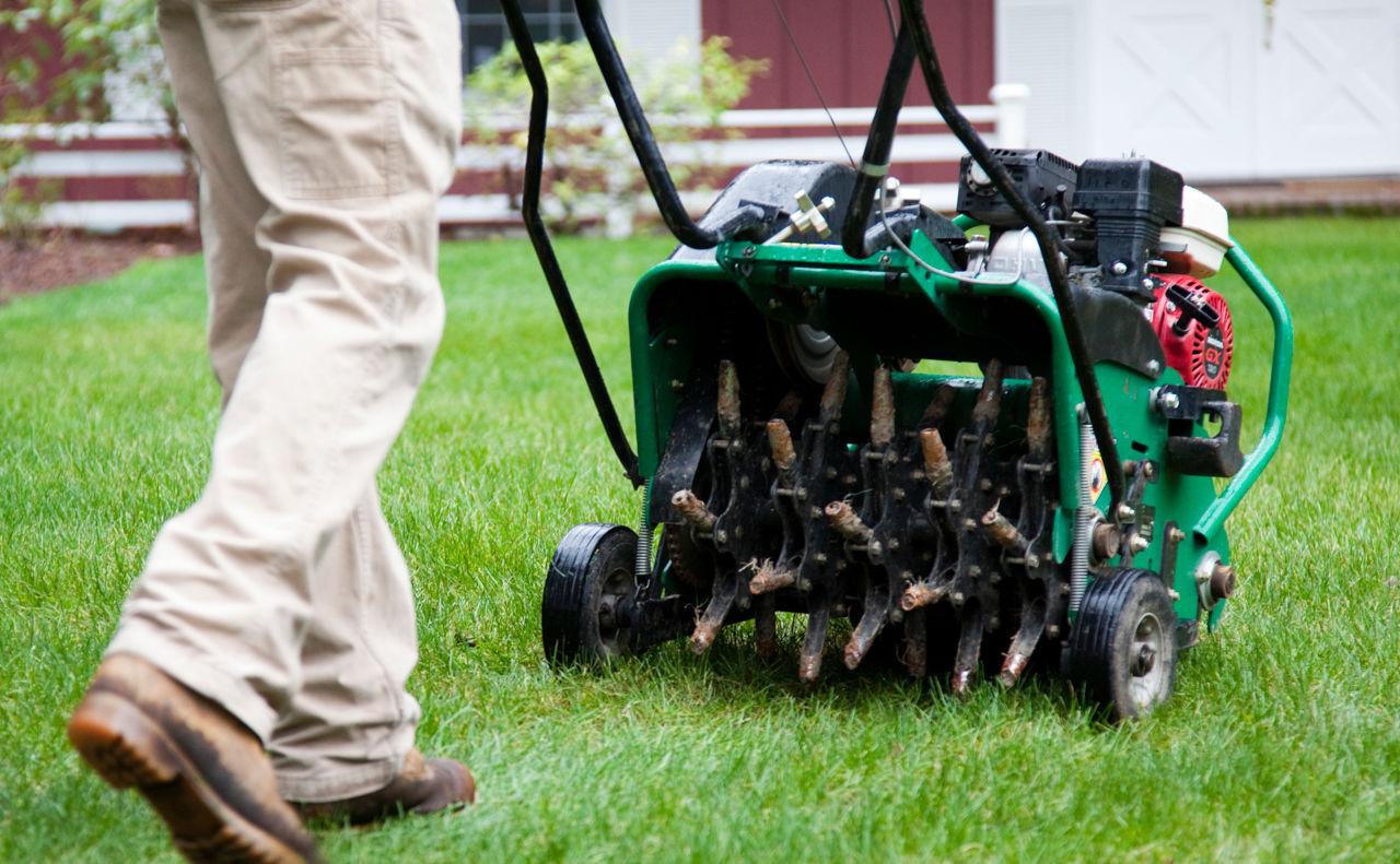 man using lawn aeration machine