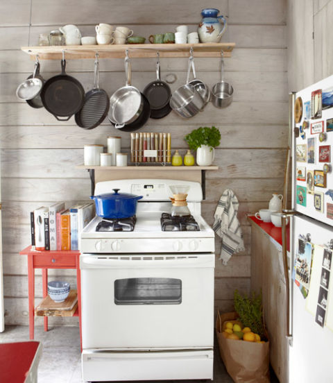 small kitchen with pots and pans on rack above the stove
