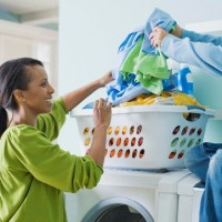 woman and his son sitting on a washer doing laundry