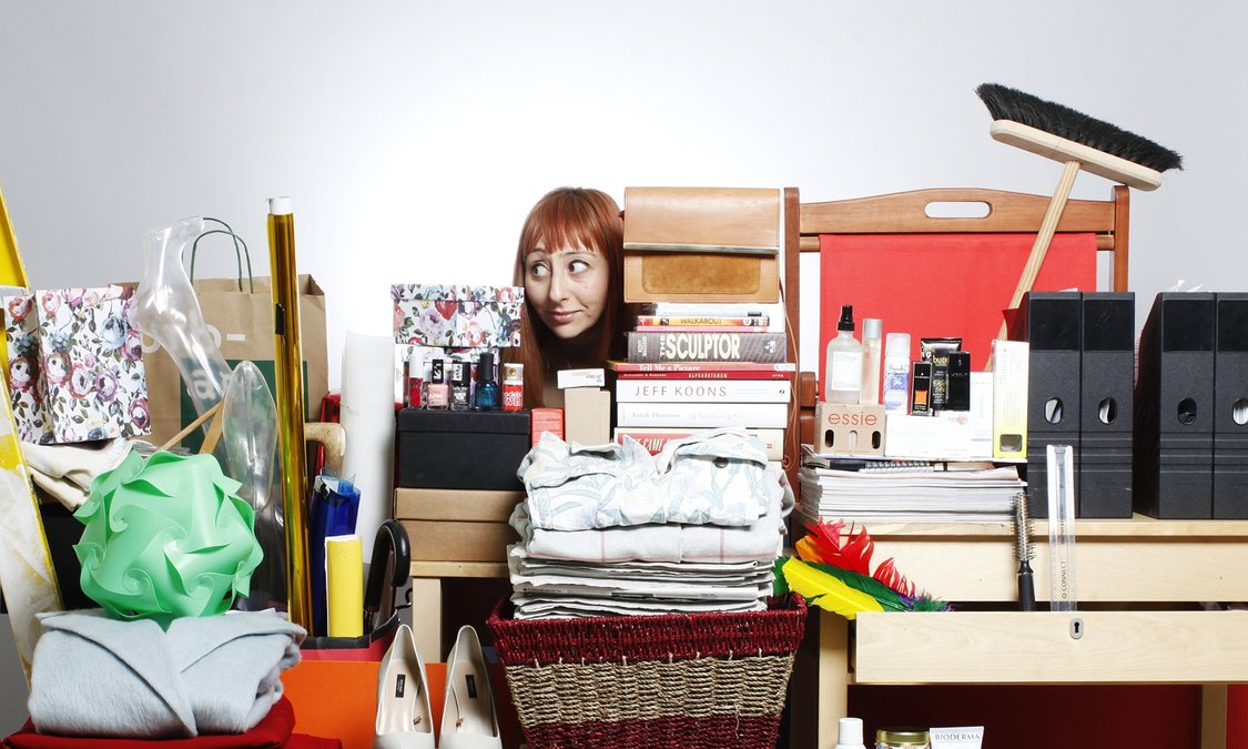woman behide a huge pile of things she needs to declutter