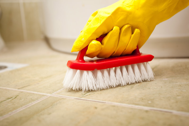... Hand In Yellow Rubber Gloves Cleaning Bathroom Tiles With A Brush