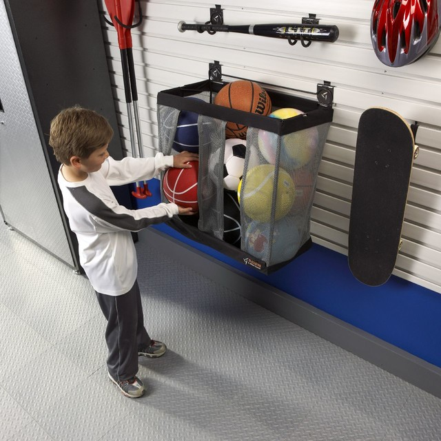 boy taking out a ball from storage basket in garage