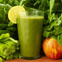 glass of green smoothie with a lot of greens, apple and lemon standing on table
