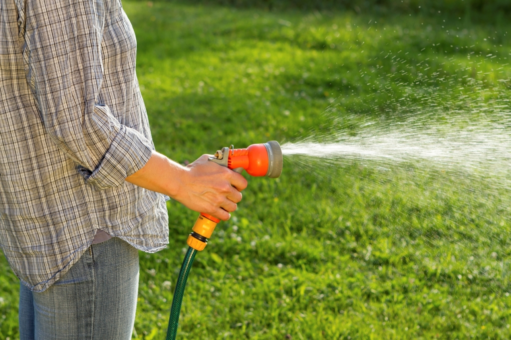man hand watering his lawn with a hose