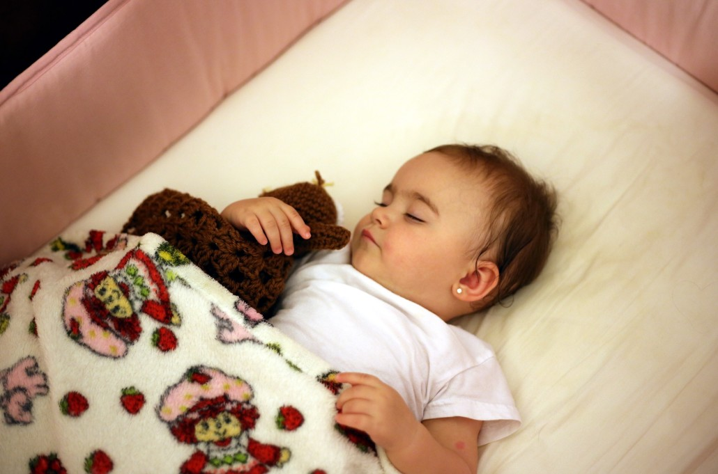 ... Baby Sleeping In Crib And Cuddling A Toy