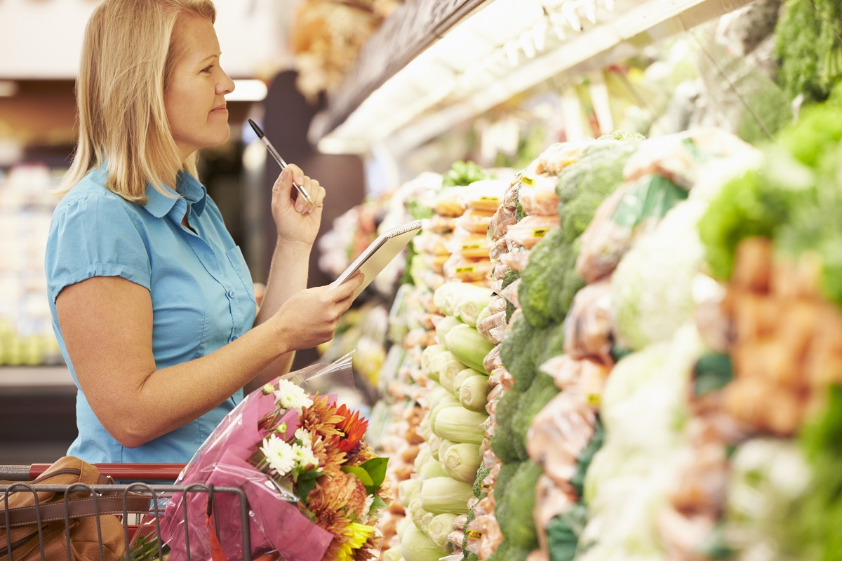 woman shopping for groceries with a grocery list