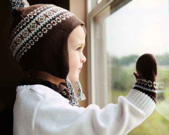 child in hat sitting on the windowsill