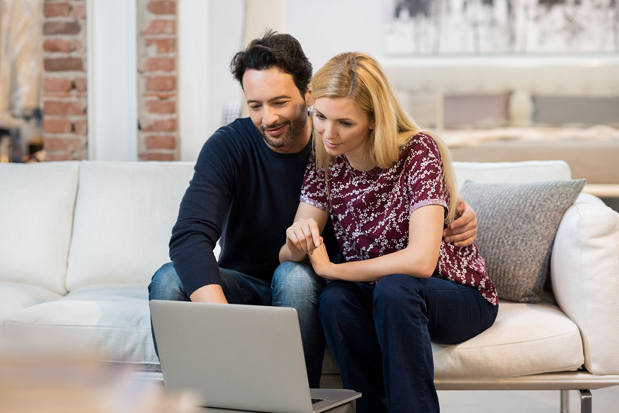 man and woman using laptop to compare prices of hiring movers