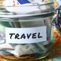 budget travel glass jar with money on the world map