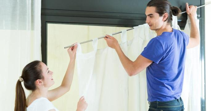 man and woman hanging curtains