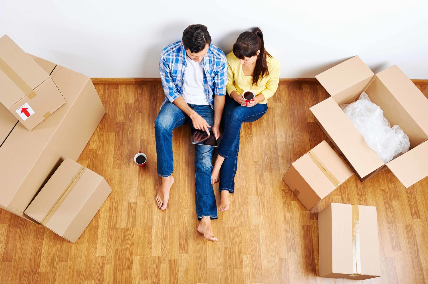young couple sitting on the floor near the boxes choosing movers on tablet