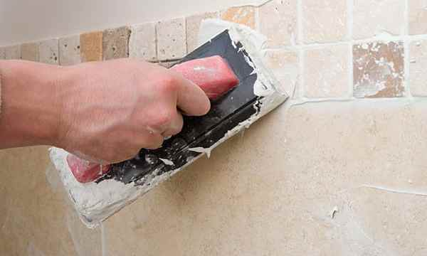 man using rubber grout float to regrout tile