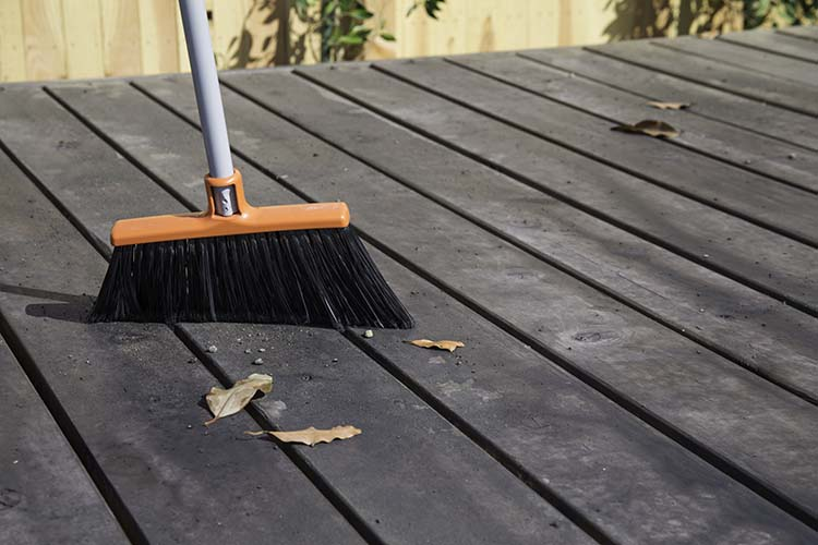 sweeping wood deck with a broom