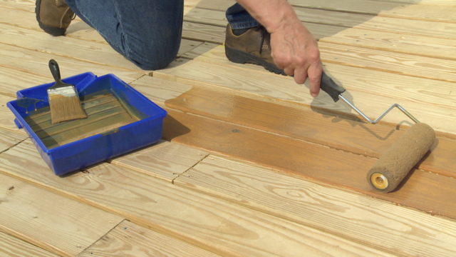 man staining wood deck with paint roller