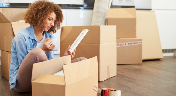 Young Woman Sitting Among Boxes Moved In Her Apartment
