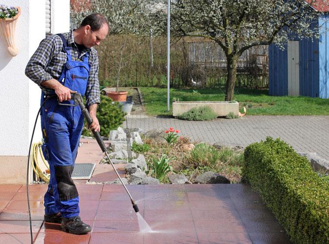 man power washing patio during spring yard cleaning