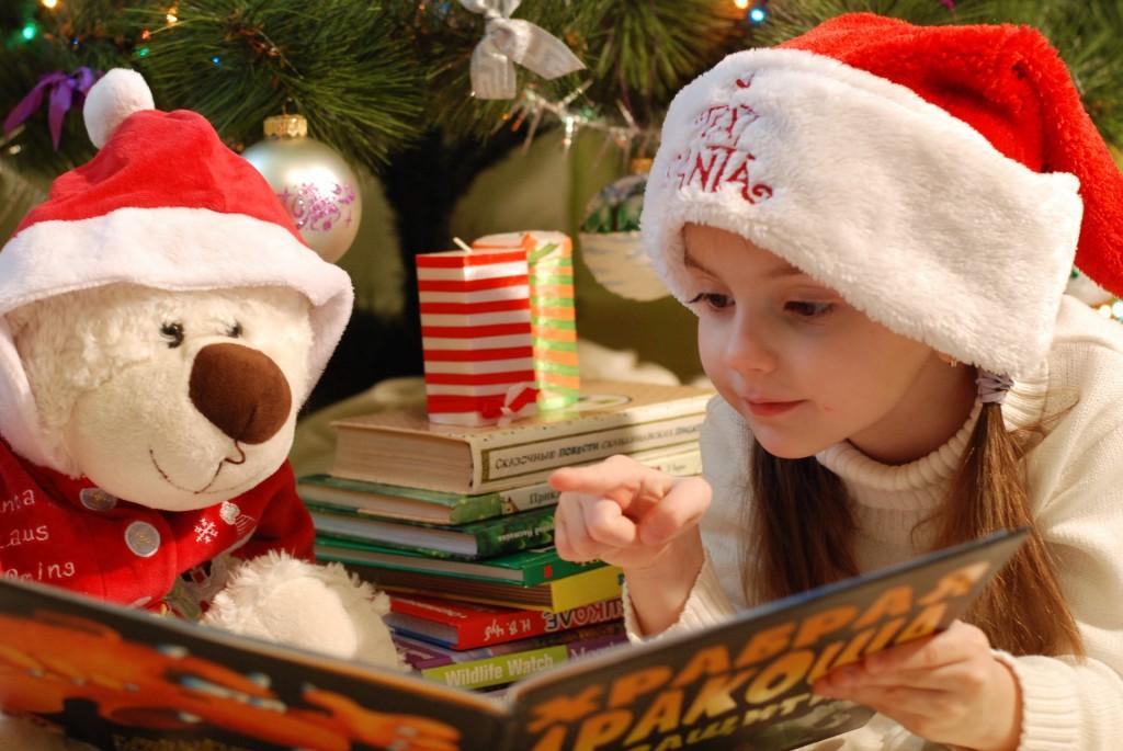 girl reading a book to a teddy bear